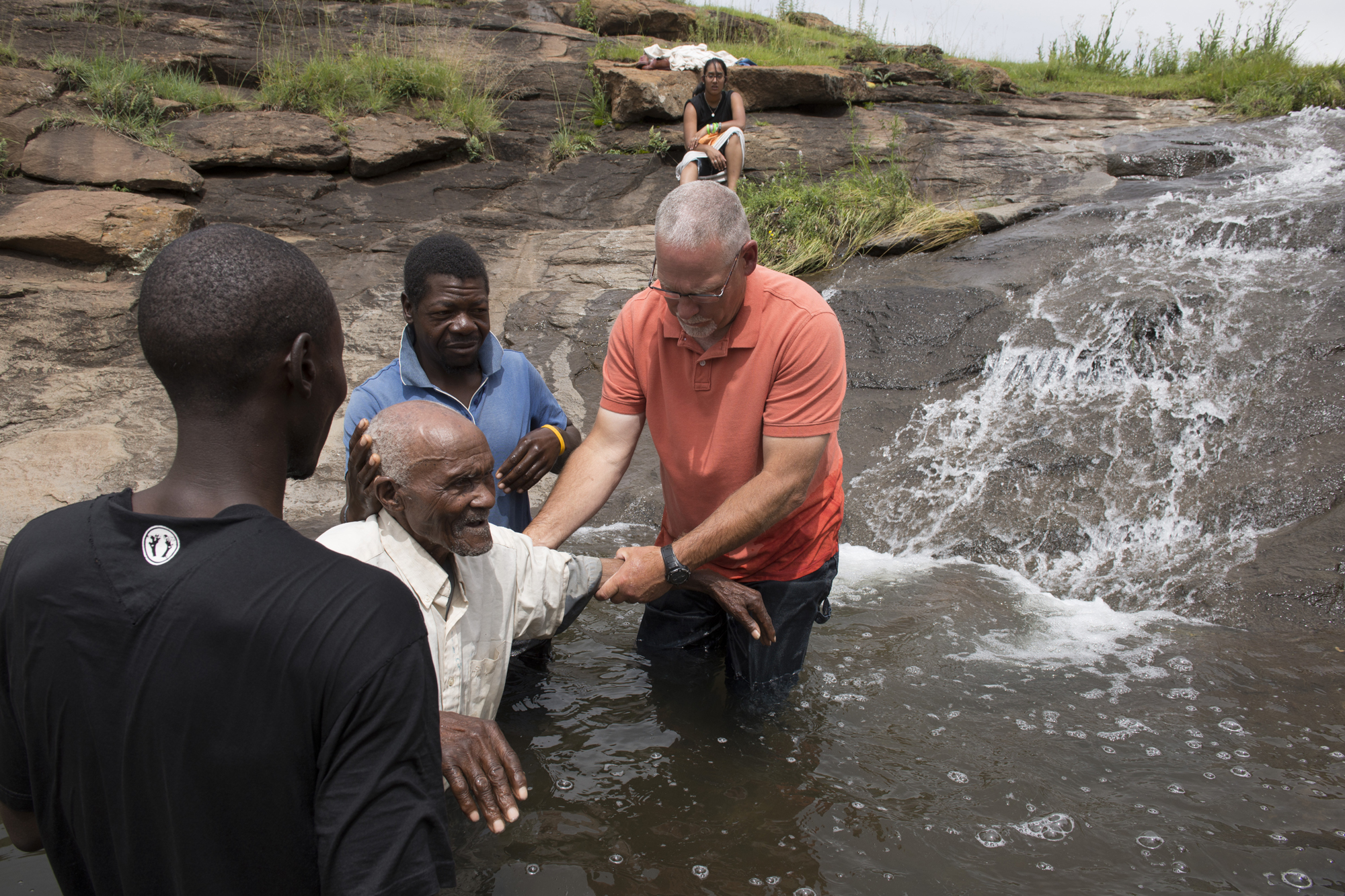 After a mile hike over steep terrain, IMB missionary Jim Flora assists local pastors as they baptize an 87-year-old believer whom they call ÒKing George.Ó When the hike became too hard for George, friends carried him on their backs to the cold mountain river.